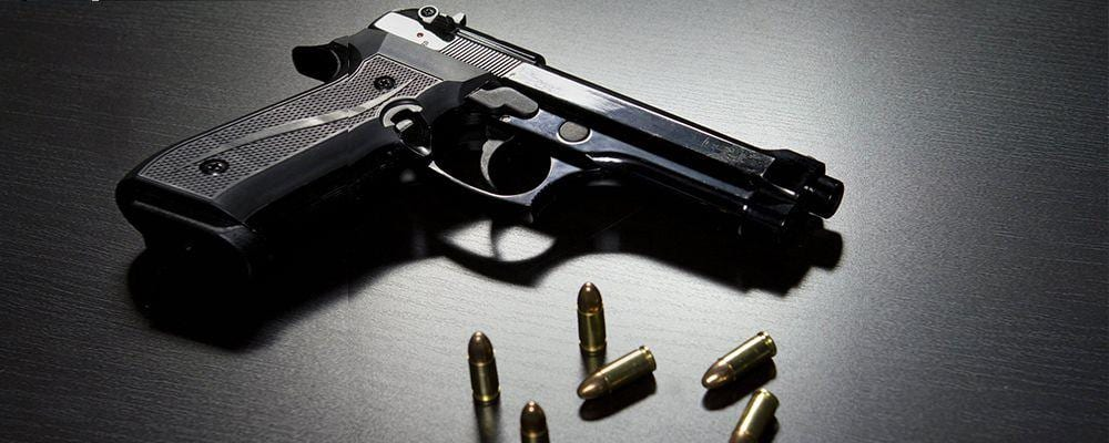 image of firearm and bullets